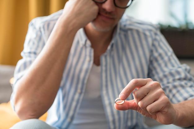 Homem close-up, segurando seu anel de casamento