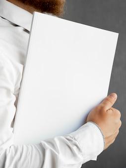 Homem close-up, segurando uma pilha de maquete de papel