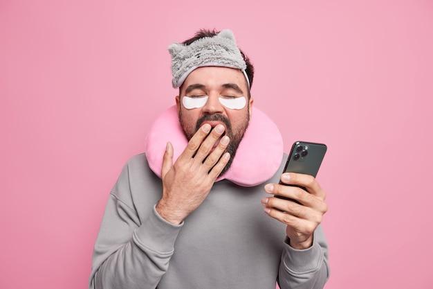 Homem cobre a boca com a mão quer ter resto pergaminhos redes sociais via smartphone aplica adesivos para reduzir o inchaço sob os olhos usa máscara de dormir com travesseiro de viagem em volta do pescoço.