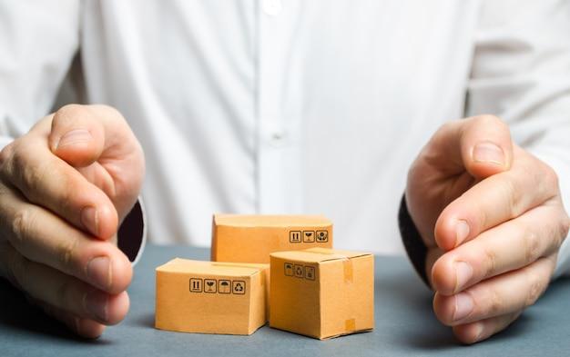 Homem cobre as mãos com caixas de papelão ou mercadorias