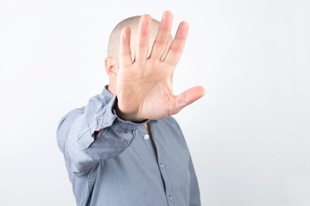 Homem cobre o rosto com a mão