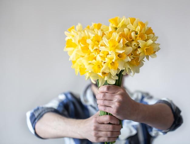 Homem cobre o rosto com um buquê de flores.