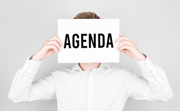 Homem cobre o rosto com um papel branco com o texto agenda