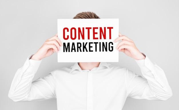 Homem cobre o rosto com um papel branco com texto marketing de conteúdo