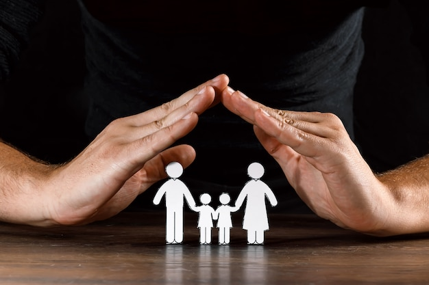 Homem cobre uma família de papel com as mãos