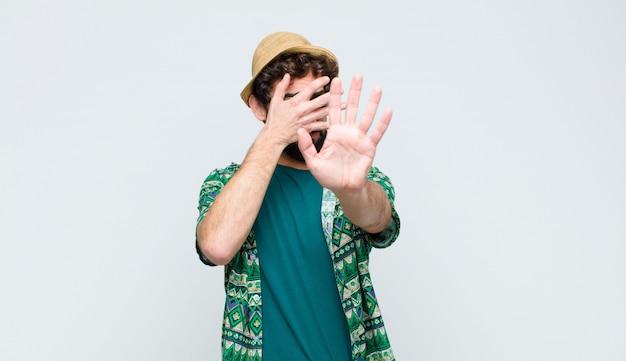 Homem cobrindo o rosto com a mão e colocando a outra mão na frente para parar, recusando fotos ou imagens
