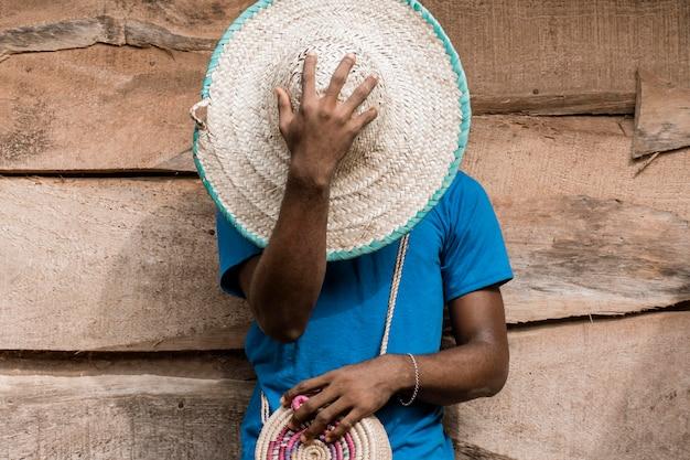 Homem cobrindo o rosto com chapéu