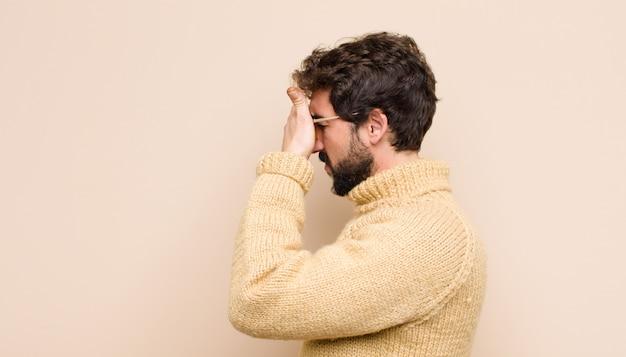 Homem cobrindo os olhos com uma mão, sentindo-se assustado ou ansioso, imaginando ou esperando cegamente por uma surpresa