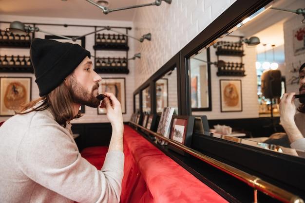 Homem coçando a barba perto do espelho