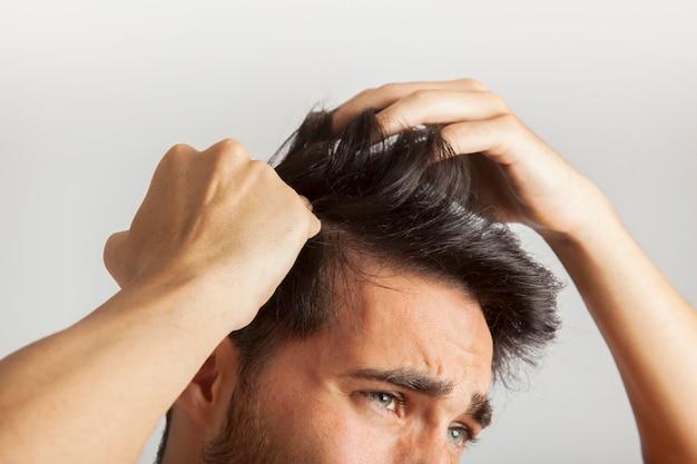 Homem coçando a cabeça