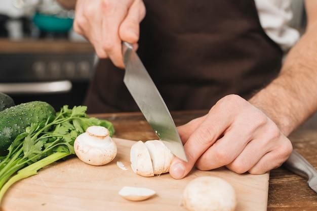 Homem, cogumelos cortantes