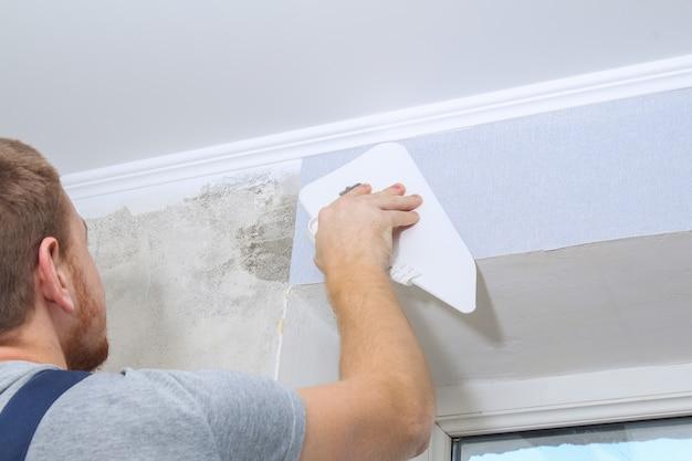 Homem cola papel de parede de vinil cinza em fundo não tecido