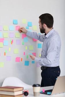 Homem colando notas adesivas na parede, no escritório