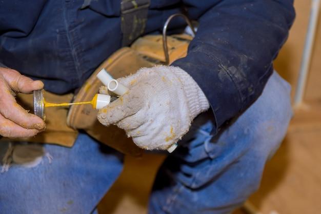 Homem colando peças de cimento cola de um pedaço de tubos de polipropileno para instalação da linha de água de uma nova casa em construção