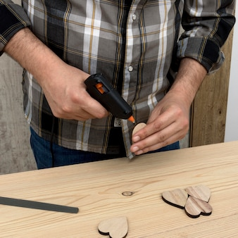 Homem colando um pedaço de madeira