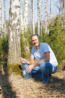 Homem coleta seiva de bétula na floresta da primavera