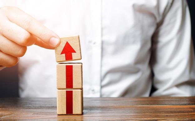Homem coleta uma torre de blocos com uma flecha passo a passo crescimento da carreira conceito de desenvolvimento