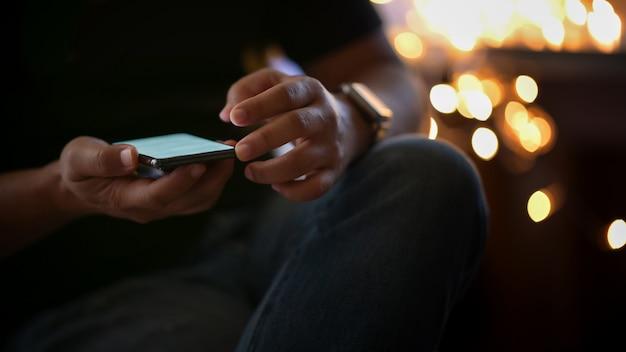 Homem colhido do tiro que usa o telefone celular na noite da rua da caminhada.