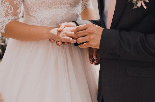 Homem coloca aliança de casamento na mão de mulher