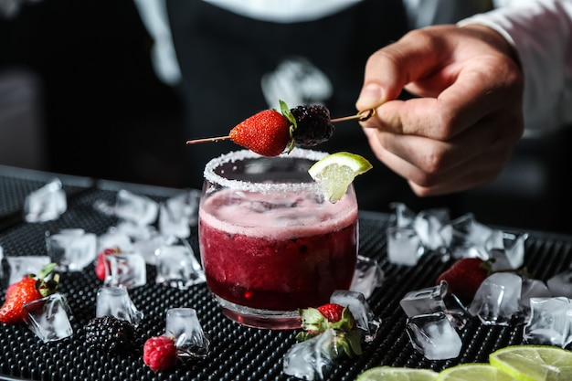 Homem coloca baga no berry cocktail álcool framboesa amora limão gelo vista lateral