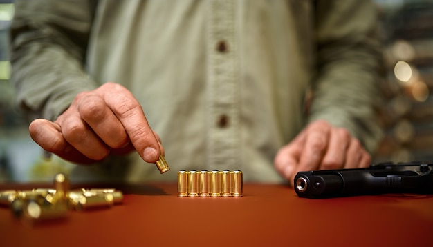 Homem coloca balas no balcão da loja de armas. interior da loja de armas, sortimento de munições e munições, escolha de armas de fogo, hobby de tiro e estilo de vida, autoproteção