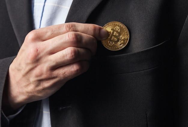 Homem coloca bitcoin no bolso da jaqueta.