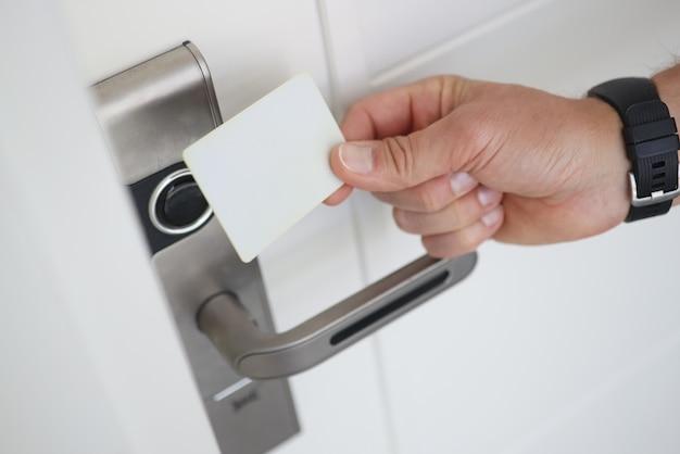 Homem coloca chave magnética na fechadura eletrônica