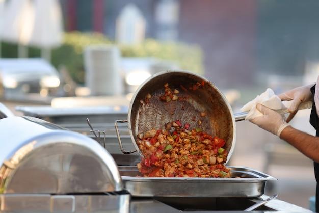 Homem coloca comida cozida da frigideira em um recipiente de metal.