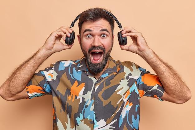 Homem coloca fones de ouvido e exclama em voz alta tem barba espessa ouve música vestido com uma camisa casual colorida isolada em bege