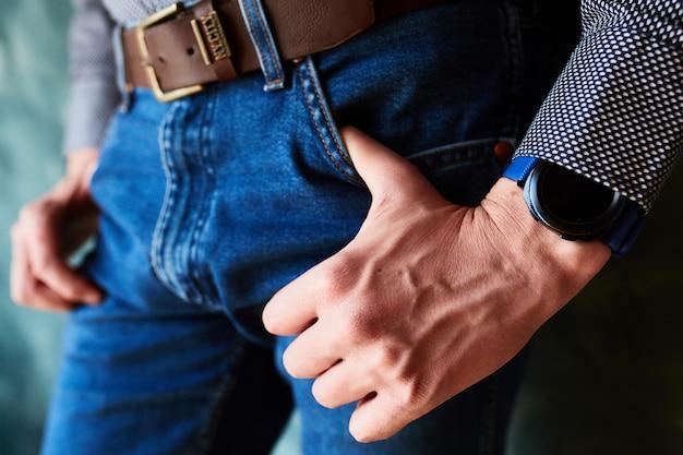 Homem coloca os polegares nos bolsos da calça jeans