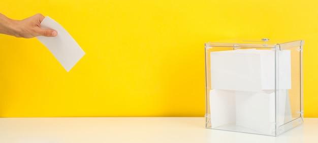 Homem colocando a cédula na urna na superfície amarela