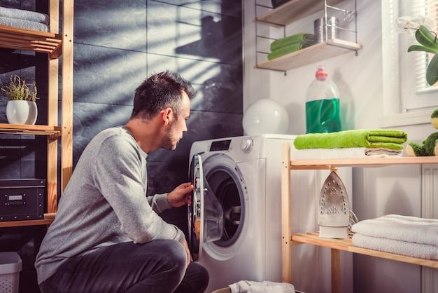 Homem colocando as roupas na máquina de lavar