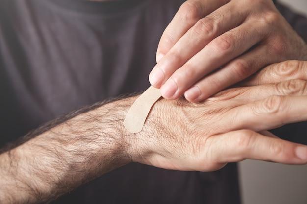 Homem colocando bandagem adesiva na mão.