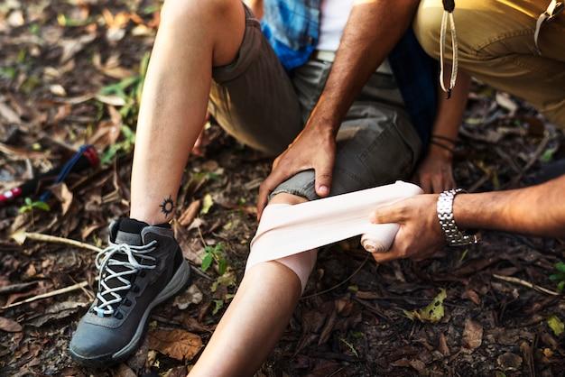 Homem colocando bandagem no joelho do seu parceiro na selva