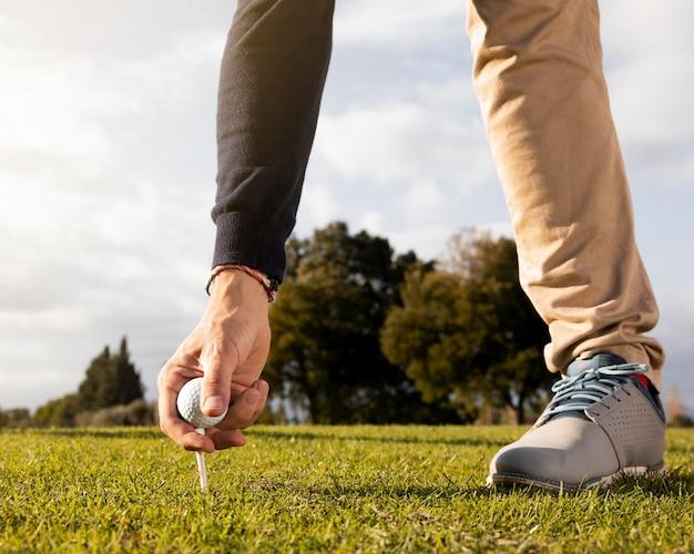 Homem colocando bola de golfe no tee