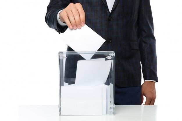 Homem colocando cédula na urna isolada