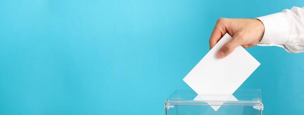 Homem colocando cédula na urna na superfície azul