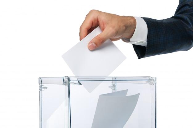 Homem colocando cédula na urna