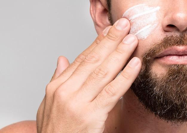Homem colocando creme no rosto, close-up