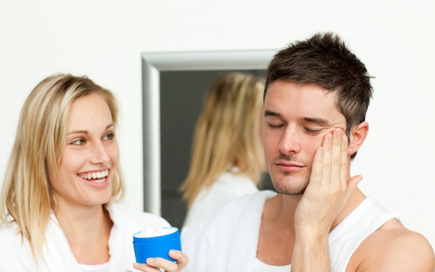 Homem colocando creme no rosto com a esposa