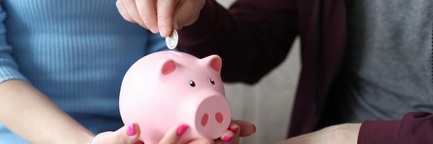 Homem colocando moedas no cofrinho rosa nas mãos da esposa, close up
