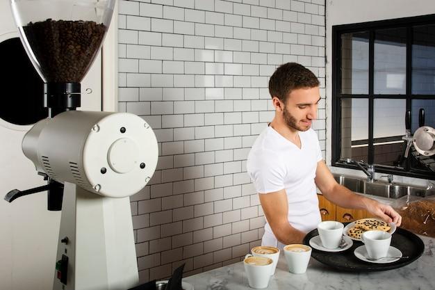 Homem colocando na bandeja xícaras de café e biscoitos