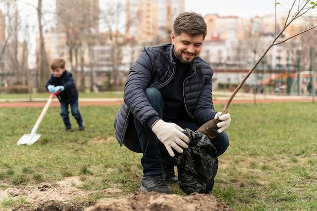 Homem colocando no chão uma pequena árvore