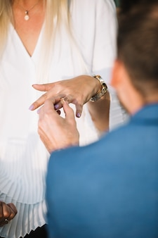 Homem colocando o anel de noivado no dedo da namorada