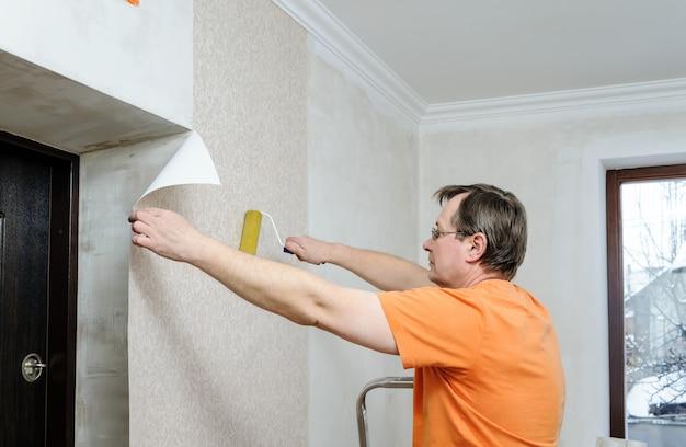 Homem colocando papel de parede em casa