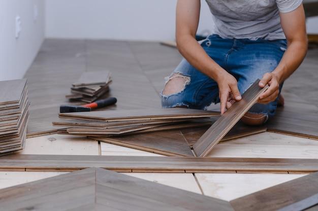 Homem colocando piso laminado - close-up em mãos masculinas