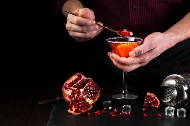 Homem colocando romã em copo de cocktail