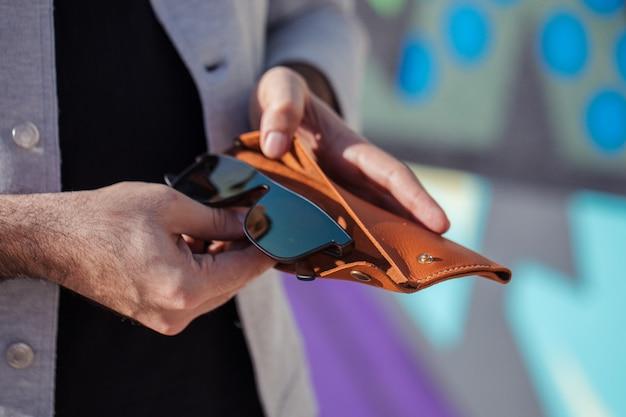 Homem colocando seus óculos de sol da moda na caixa