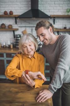 Homem colocando smartwatch na mão da mãe