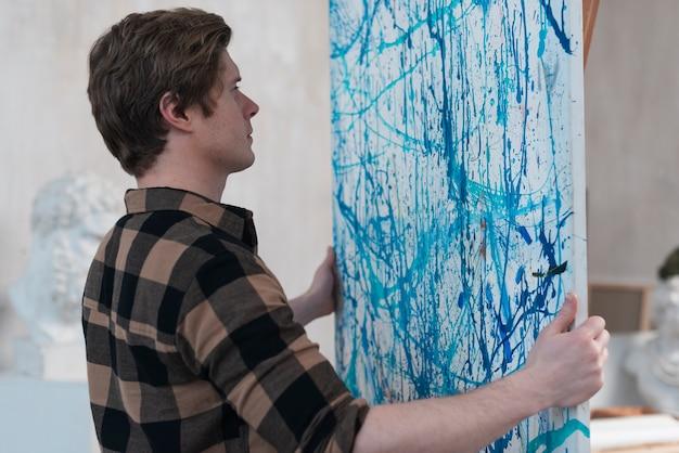 Homem colocando sua pintura em um cavalete